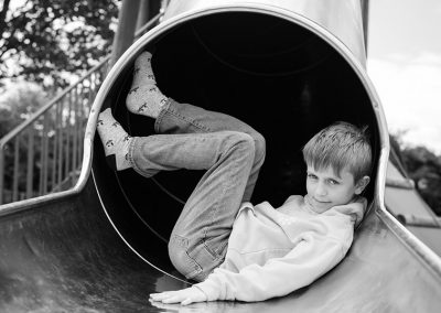A black and white image of a boy in a Hitchin playground relaxing and smiling at the camera
