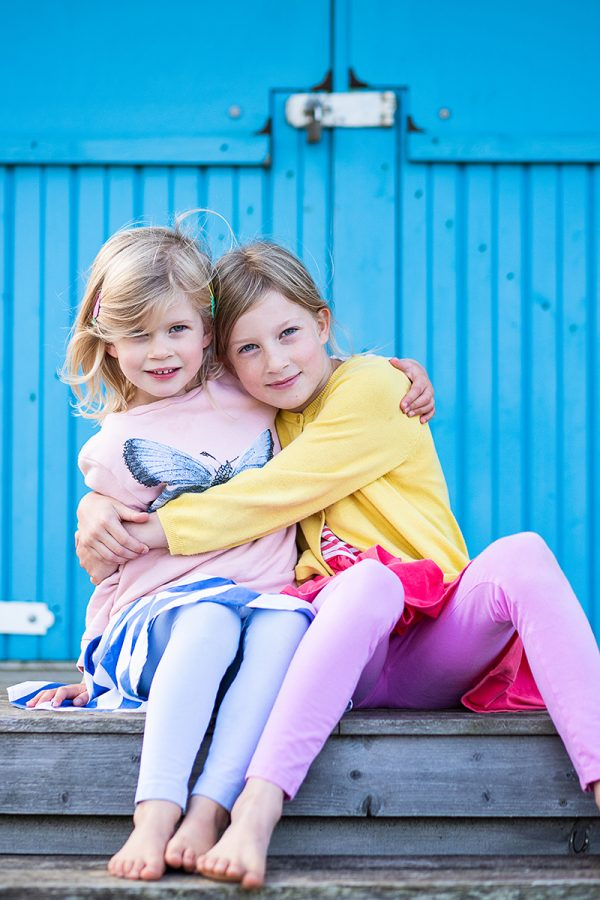 An image of 2 sisters sitting outside a colourful beach hut