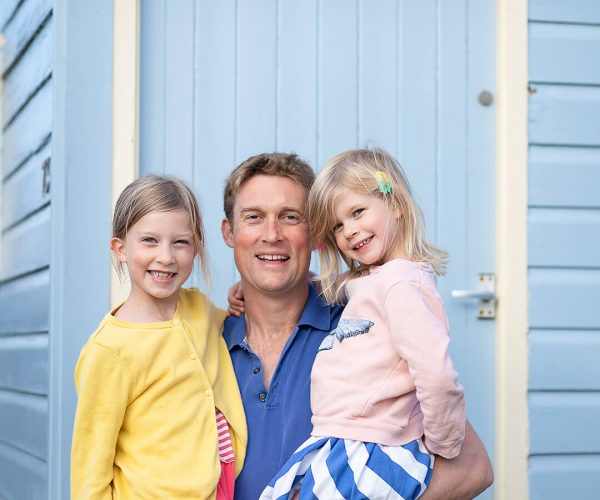 A father and his daughters pose infront of a colourful beach hut in Norfolk