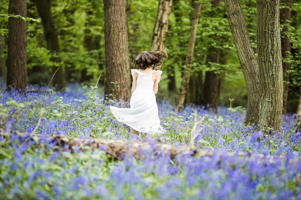 A girl in the bluebells wearing a white dress