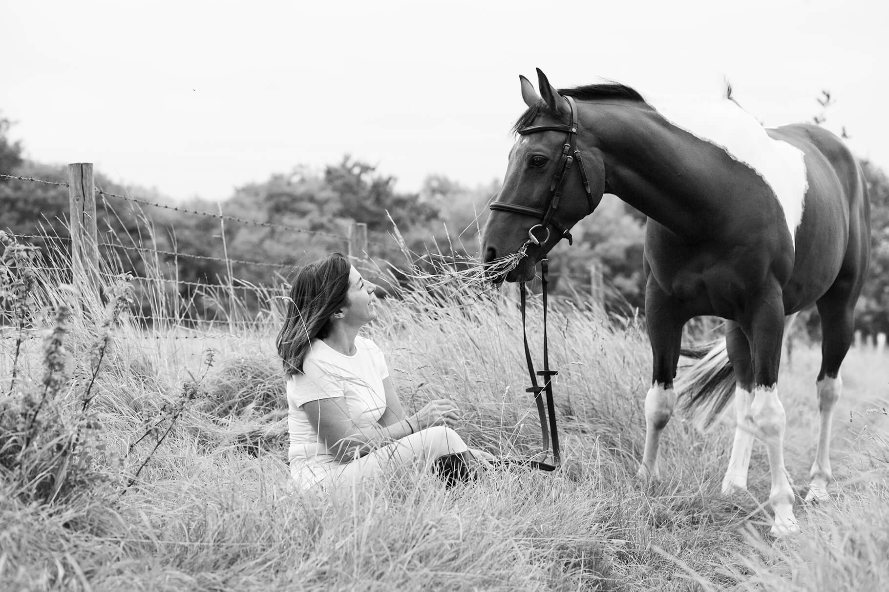 A black and white image of a horse and it's owner taken outside in nature