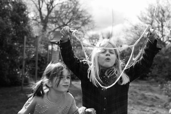 An image of two friends in a garden blowing bubbles