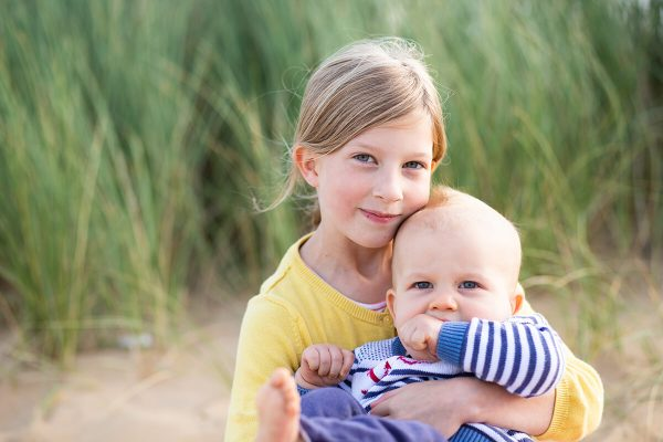 An image of a baby and his big sister smiling on the beach in Norfolk
