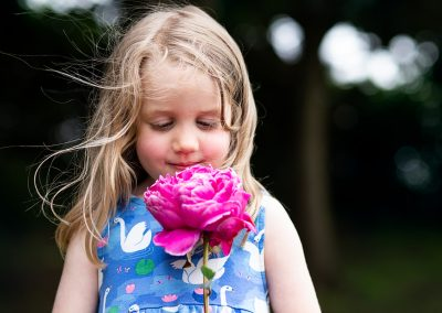 Girl in a blue dress holds a pink peony flower